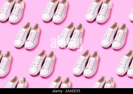 Pattern made of of many white trendy sneakers on pink pastel background. Open composition. Flat lay style. - Stock Photo