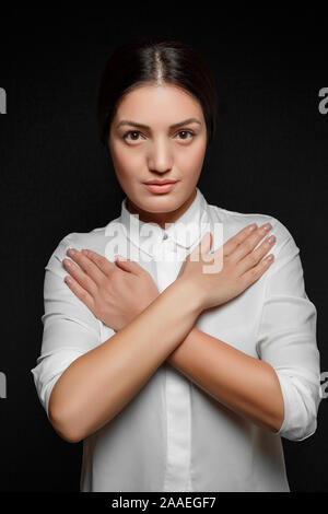 portrait of Asian brunette woman in white shirt with arms crossed on chest on black background - Stock Photo