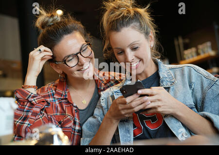 Relaxed friends smiling looking at cellphone in coffee shop - Stock Photo