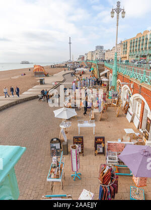 A small market beside the beach at Brighton.  Shoppers view the souvenirs on sale and people also walk along the pavement. - Stock Photo