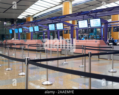 SINGAPORE - 4 OCT 2019 - Empty check-in counters at Singapore Changi Airport Terminal 1 Departure Hall with no passengers in sight - Stock Photo