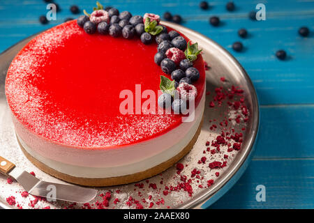 Cheesecake with blueberries on an iron plate on a blue wooden background. - Stock Photo