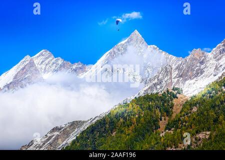 Paraglider over mountain snow peak, Swiss Alps, Zermatt, Switzerland - Stock Photo