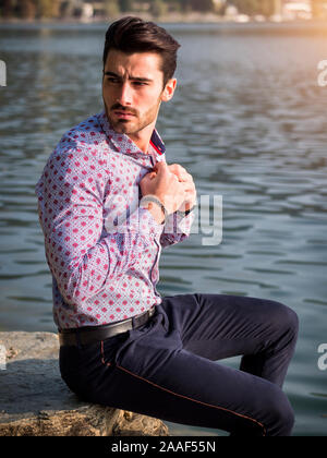 Young man wearing beside picturesque river or lake - Stock Photo