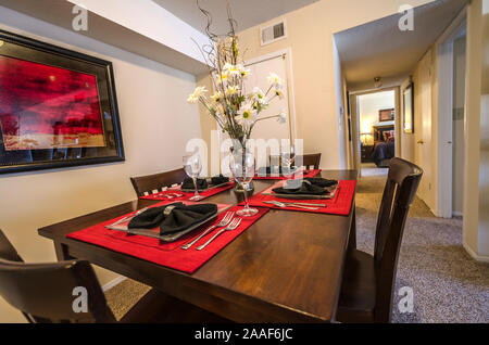 Red placemats complement the artwork in a dining room at Four Seasons apartments in Mobile, Alabama. - Stock Photo