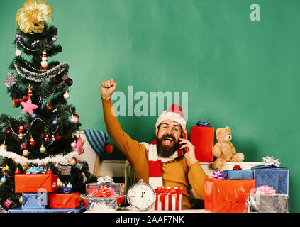 Man with beard and cheerful face sends greetings. Santa holds cellphone and puts hands up. Santa Claus talks on mobile phone near fir tree on green background. Winter holiday and technologies concept - Stock Photo