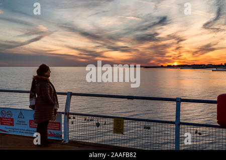 A woman looks out across the sea to the sun setting behind a coastal town. Concept of sun setting on a relationship, falling out of love, breaking up. - Stock Photo