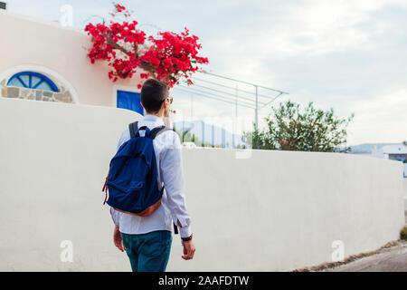 Man traveler walking in Akrotiri village on Santorini island, Greece. Tourist admiring architecture landscape