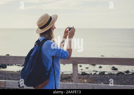 Woman traveler walking on Vlychada beach in Akrotiri on Santorini island, Greece. Tourist taking photo of sea