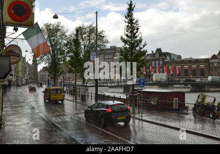 Amsterdam, Holland. August 2019. A rainy day: cars raise water splashes. In the distance the sky is clearing. - Stock Photo