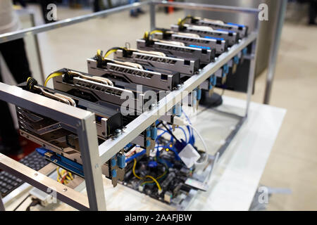 Crypto currency ethereum mining equipment rig - lots of gpu cards on mainboard. Graphics processing units connected to motherboard with cables. Server - Stock Photo