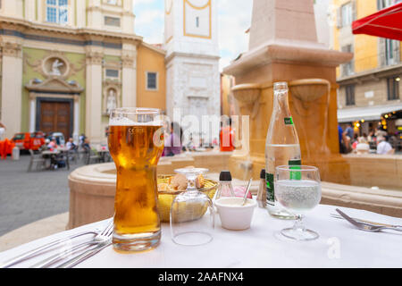 A basket of bread and rolls, a glass of beer and a bottle of water on a patio table in a piazza in front of a fountain in Nice France. - Stock Photo