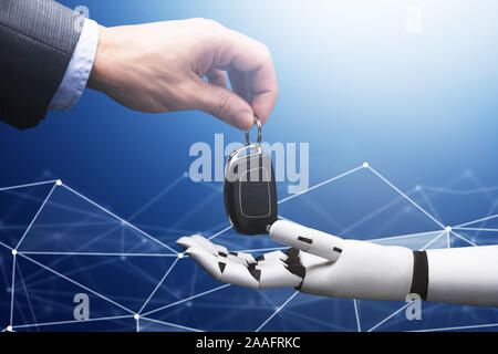 Close-up Of A Businessperson's Hand Giving Car Key To Robot On Blue Technology Background Stock Photo