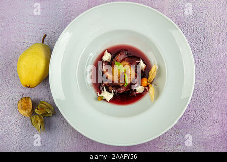 Plate of pears poached in red wine, dessert decorated with on wooden table. - Stock Photo