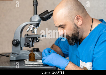 Male laboratory assistant examining biomaterial samples in a microscope - Stock Photo