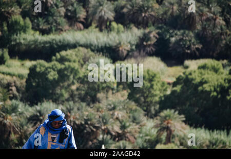 Merzouga, Errachidia / Morocco - 10 03 2019: Arab man dressed in blue with an oasis in the background - Stock Photo