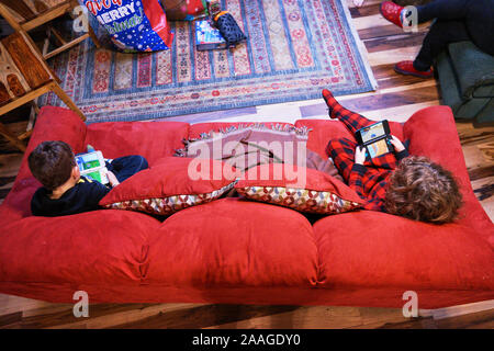 Two boys sitting on a red sofa and playing handheld video games during Christmas holidays in Willits, California. - Stock Photo