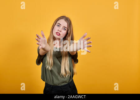 Attractive woman wearing shirt spreading hands, and looking so funny, serious - Stock Photo