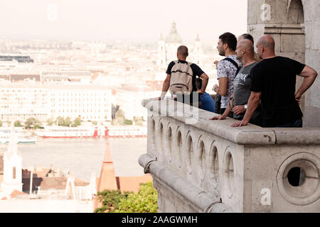 Budapest, Hungary - May 27, 2019: tourists stand on balcony looking out over a sunny city - Stock Photo