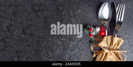 Banner of Festive Christmas table place setting with cutlery, pine branche, red berries, rose hip, cone in burlap bag. Winter holidays and festive - Stock Photo