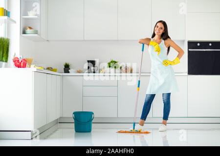 Full length photo of positive cheerful housewife wearing yellow rubber gloves enjoy washing floor hold mop feel content wearing denim jeans casual - Stock Photo