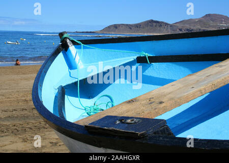 Blue fishing boat lying on the sand beach - Stock Photo