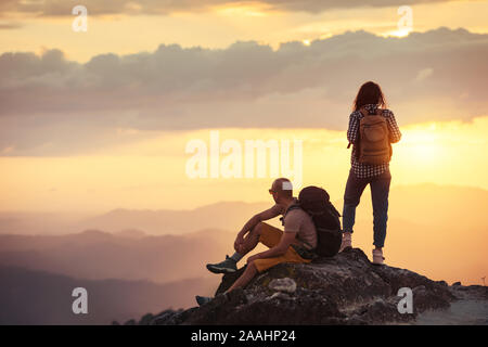 Couple hikers with backpacks are having rest on mountain top at sunset time - Stock Photo