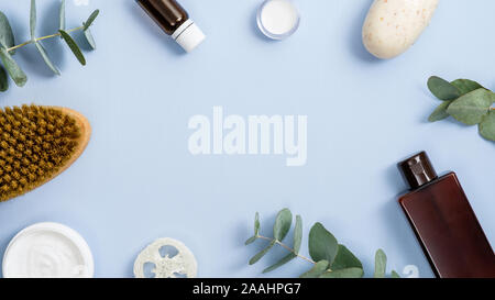 Frame made of organic spa cosmetics and accessories on blue background. Flat lay, top view, copy space. Zero waste bathroom essentials, plastic free i - Stock Photo