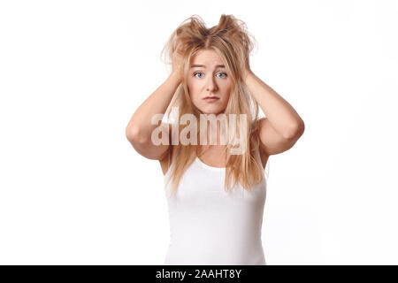 Young woman in white shirt disappointed with her messy and disheveled blond hair, standing with her arms to her head, looking at camera with sad emoti - Stock Photo