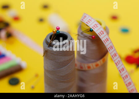 Sewing buttons and threads on a yellow background. Needlework concept. A lot of multi-colored little bobbins of sewing thread on a yellow background.