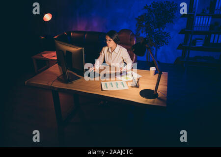 Nice attractive stylish lonely single lady top executive manager marketer financier analyzing startup financial result preparing daily report at night - Stock Photo