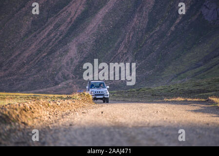 Off road vehicle on dirt road, mountain in background, Landmannalaugar, Highlands, Iceland - Stock Photo