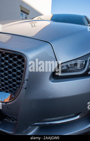 Car Crash: Damage and close up details, silver Jaguar. Road traffic accident. Crushed metal and plastic. - Stock Photo