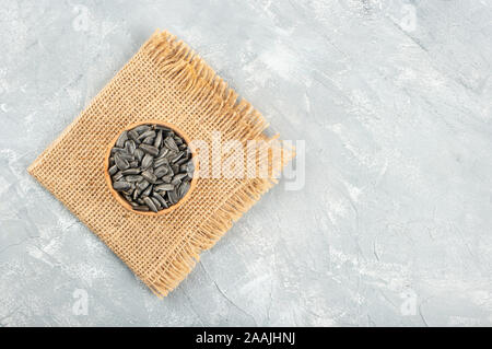 Sunflower seeds in wooden bowl on burlap and concrete background - Stock Photo