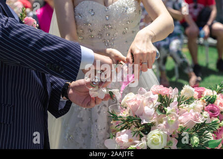 Couple pour two color sand from both cup into one cup in wedding ceremony - Stock Photo