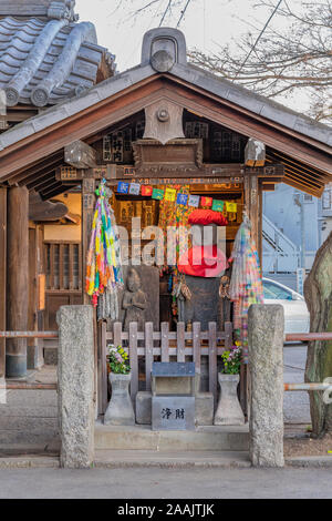 Shrine dedicated to Jizo statues symbol of filial piety to protect children and decorated with thousnd cranes origami in the Tennoji Temple of Yanaka - Stock Photo