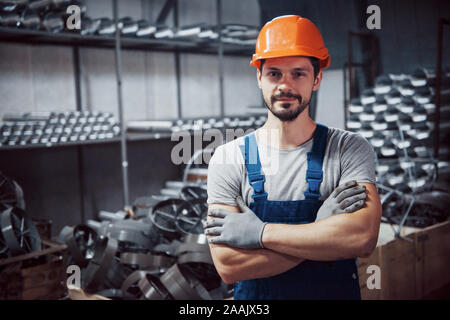 Portrait of a young worker in a hard hat at a large metalworking plant. Shiftman on the warehouse of finished products - Stock Photo