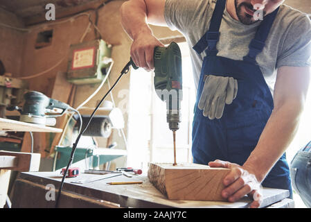 The master works in a studio and drill a hole in a wooden board. - Stock Photo