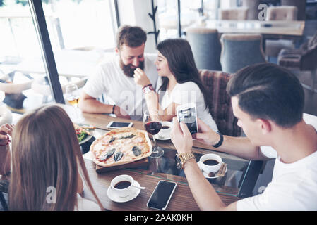 Tasty pizza on the table, with a group of young smiling people resting in the pub - Stock Photo