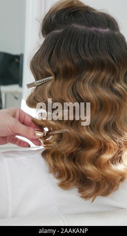 Hairdresser's hands putting clasps in a client's hair. - Stock Photo