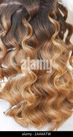 Silver hairdressers clips in curly hair. - Stock Photo