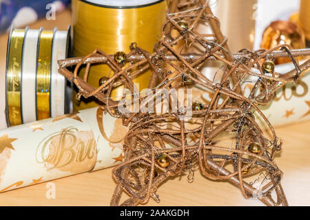 Wooden star in front of various materials such as wrapping paper and ribbons to pack and decorate Christmas presents. - Stock Photo