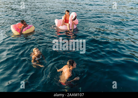Friends swimming and relaxing on floats on sea, Italy - Stock Photo