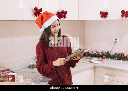 Woman standing in decorated for Christmas kitchen - Stock Photo