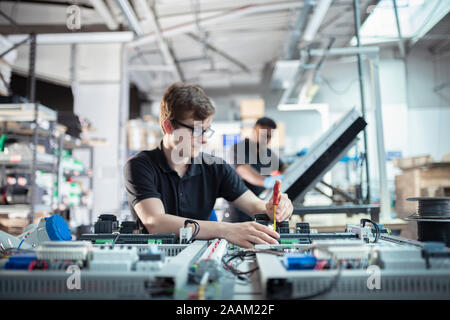 Apprentice electronics engineers in electronics assembly factory - Stock Photo