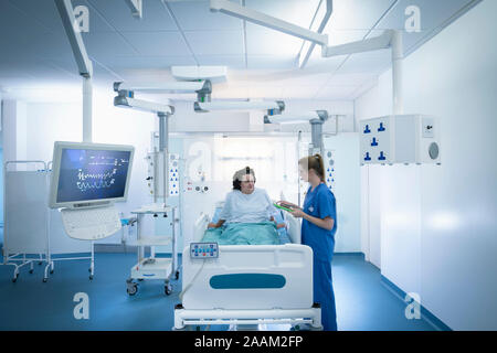 Nurse and patient in intensive care unit in hospital setting - Stock Photo