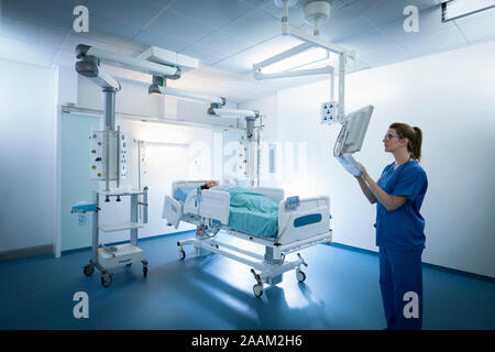 Nurse inspecting screen in intensive care unit in hospital setting - Stock Photo
