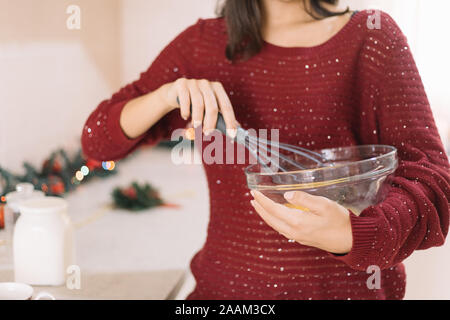 Cropped woman holding bowl and whisking eggs - Stock Photo