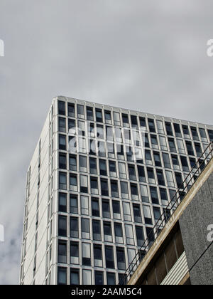 Looking upwards to a modern, white hi rise office block under a grey, cloudy sky - Stock Photo