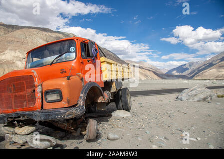 wreck of truck alongside empty road in Himalayas in Nubra valley in Ladakh, India - Stock Photo